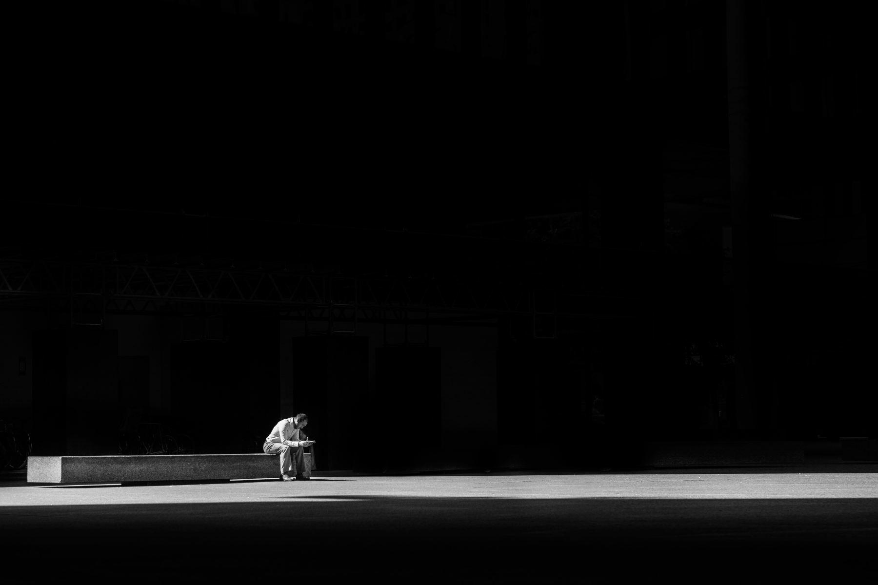 man sitting alone on concrete bench