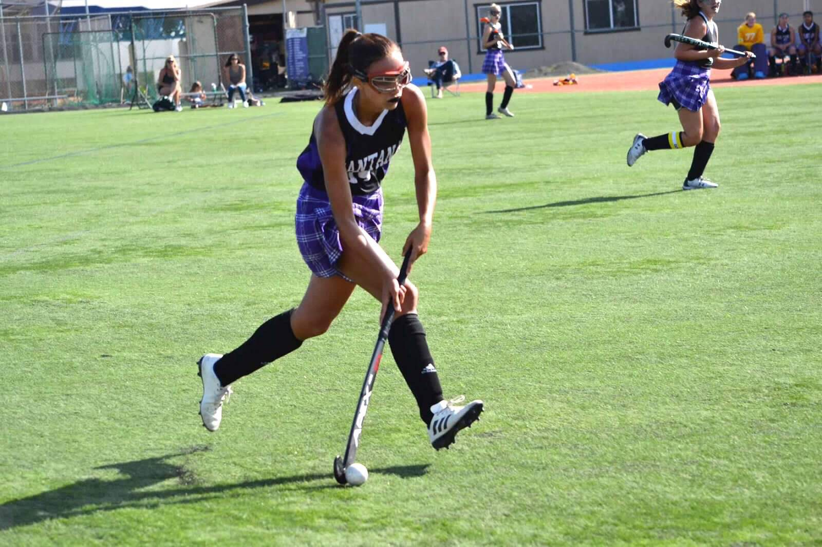 A girl playing field hockey, mid swing on the ball.