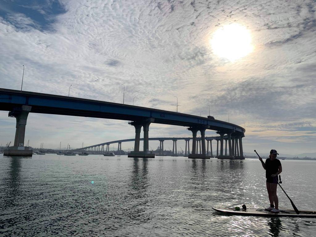 woman on a paddleboard in front of Coronado Bridge in San DIego